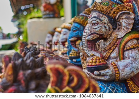 Typical souvenir shop selling souvenirs and handicrafts of Bali at the famous Ubud Market, Indonesia. Balinese market. Souvenirs of wood and crafts of local residents. Wooden statues made from wood. #1064037641