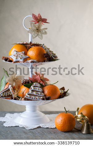 Typical traditional german Christmas cookies with icing, tangerine and decorations in white metal etagere on the wooden table with creme background, vertical