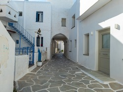 Typical urban Cyclades architecture with whitewashed stonewall houses empty cobblestone narrow alley ways under covered shelters with arches at Kythnos island, Chora village Greece. Summer destination