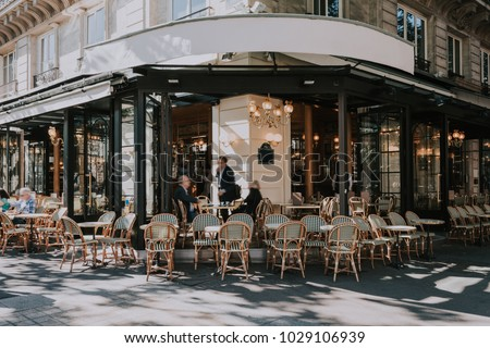 Typical view of the Parisian street with tables of brasserie (cafe) in Paris, France. Architecture and landmarks of Paris. Postcard of Paris