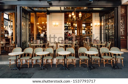 Typical view of the Parisian street with tables of brasserie (cafe) in Paris, France. Architecture and landmarks of Paris. Cityscape of Paris