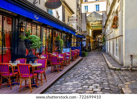 Photo of Typical view of the Parisian street with tables with tables of cafe in Paris, France. Architecture and landmark of Paris. Cozy Paris cityscape
