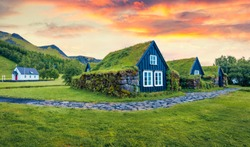 Typical view of turf-top houses in Icelandic countryside. Dramatic summer sunrise in Skogar village, south Iceland, Europe. Traveling concept background.