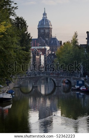 Typical view on Amsterdam, with small boats in a canal, many bicycles on a bridge and a church in the background, all lighted by the early rays of the sun