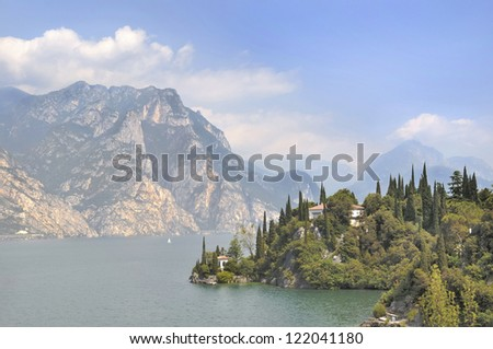 typical villa on the edge of a lake surrounded by mountains