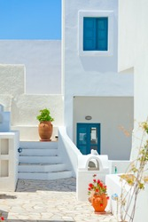 Typical white villa houses with blue windows and flower pots in Oia, Santorini