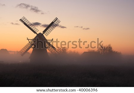 Typical windmill in the Netherlands with fog during sunrise.
