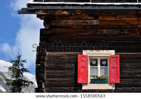 Typical wooden alpine chalet with window with red shutters. Rustical cottage with decoration in mountains Alps. Countryside in Livigno in Italy.