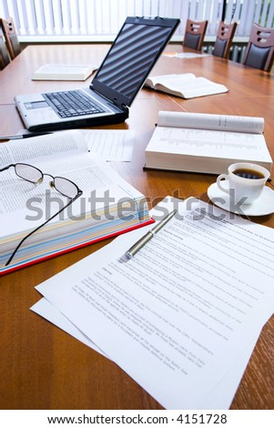Typical workplace of a busy successful business person in the morning before meeting: computer, books, pens, papers, a cup of coffee and glasses on a table