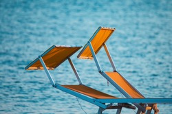 typical yellow or orange sunbeds of the Riviera Romagnola adriatic coast of Italy, with the sea in the background. Rimini Beach