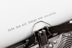 Typing a holy bible quote with God all things are possible on a vintage typewriter