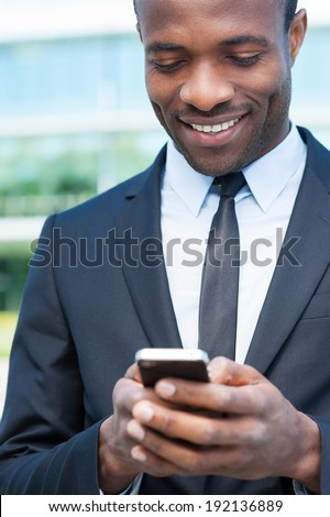 Typing business message. Cheerful young African man in formal wear holding mobile phone and smiling while standing outdoors