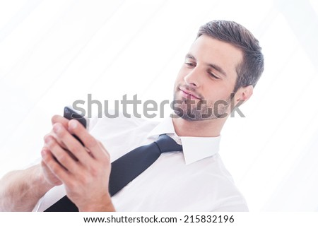 Typing business message. Low angle view of handsome young man in shirt and tie typing message on the mobile phone and smiling