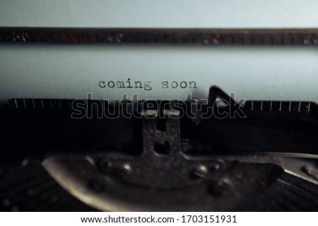 Typing 'coming soon' on retro typewriter Foto stock ©