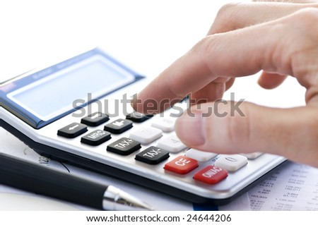 Typing  numbers for income tax return with pen and calculator
