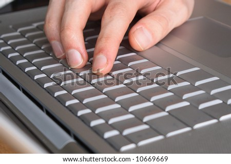 Typing on a laptop - selective focus on index finger
