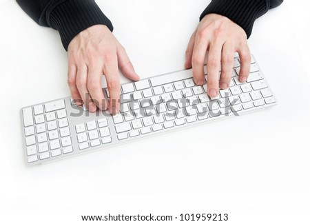 Typing on computer keyboard on a white desktop