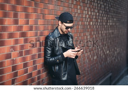 Typing text message. handsome young man in smart casual wear holding mobile phone while leaning at the brick wall