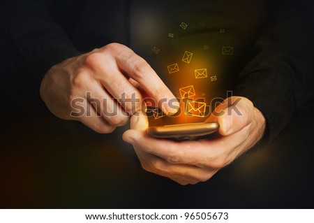 Typing text message on smartphone. Focus on hands and the phone device. Orange envelopes as incoming or outgoing messages.