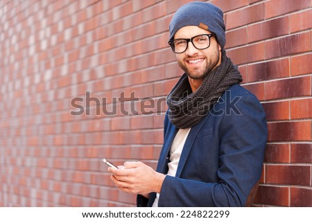 Shutterstock Typing text message. Side view of handsome young man in smart casual wear holding mobile phone while leaning at the brick wall
