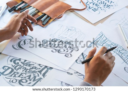 Typography Calligraphy artist designer drawing sketch writes letting spelled pen brush ink paper table artwork.Workplace design studio. #1290170173