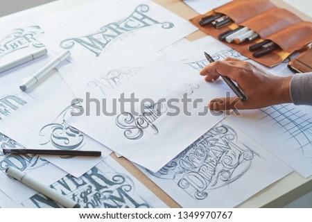 Typography Calligraphy artist designer drawing sketch writes letting spelled pen brush ink paper table artwork.Workplace design studio. #1349970767