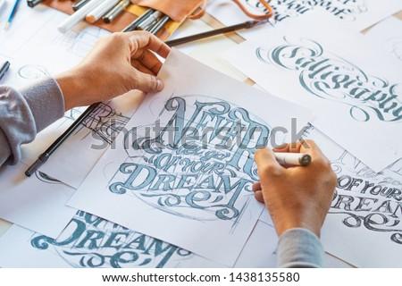 Typography Calligraphy artist designer drawing sketch writes letting spelled pen brush ink paper table artwork.Workplace design studio. #1438135580