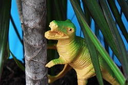 Tyrannosaurus under a tree, palm tree. Extinct animal dinosaur, toy dinosaur that lived in the Jurassic period.