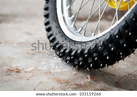 Tyre of motocross bike on ice and snow on background, selective focus on the middle part