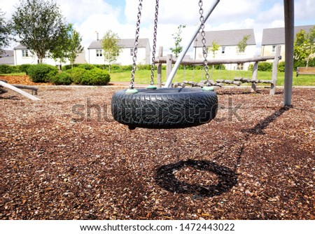 Tyre swing in a childrens play ground with other recreational equipment.  #1472443022