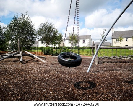 Tyre swing in a childrens play ground with other recreational equipment.  #1472443280