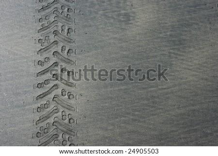 Tyre track in black beach sand horizontal