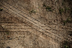 Tyre track on dirt sand or mud, Picture in retro or grunge tone. Car drive on sand. off road track. Track near grass