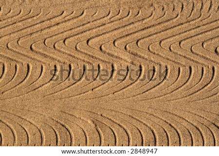 Tyre tracks in sand, making an interesting abstract pattern background.