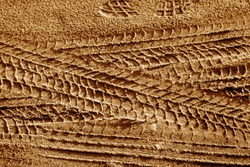 Tyre tracks on sand in brown tone. Abstract background and pattern.