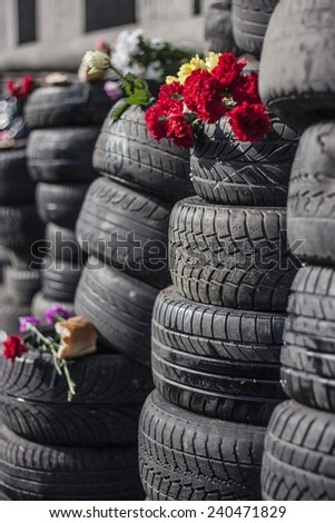 Tyres cars stacked in columns. The top is a memorial bread and flowers. Location Kiev, Maidan Nezalezhnosti. Close-up.