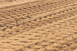 Tyres imprints on sand, abstract background.