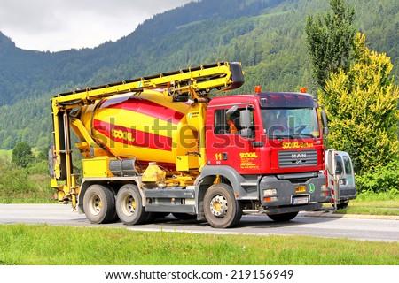 TYROL, AUSTRIA - JULY 29, 2014: Red concrete mixer truck MAN TGA at the high Alpine road.