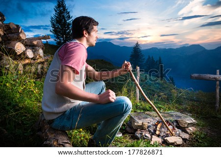 Tyrol - Young man sitting on alpine meadow of a mountain on Campfire in the Bavarian Alps and enjoys the romantic evening sunset of the panorama in leisure time or vacation