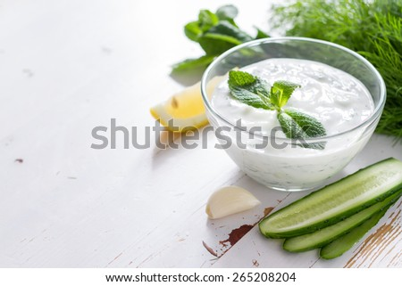Tzatziki sauce in glass bowl, with ingredients - cut cucumber, mint, dill, lemon, garlic, white wood background