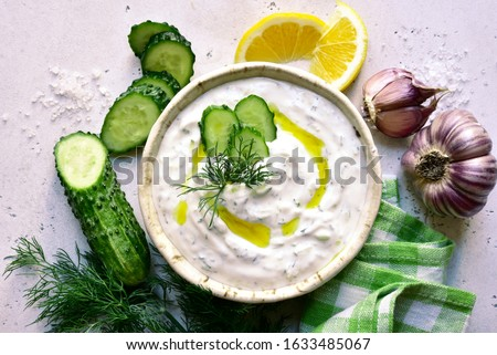 Tzatziki - traditional greek yogurt sauce in a bowl on a white slate, stone or concrete background. Top view with copy space.
