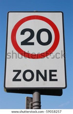 U.K. twenty miles per hour speed limit sign is shown against a bright blue sky. - stock photo