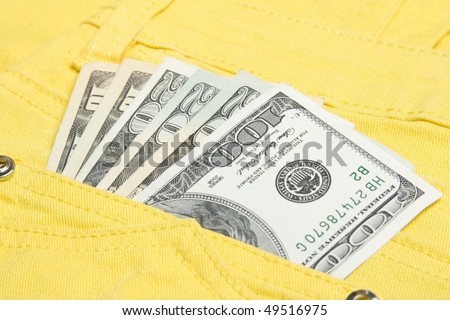 U.S. 100, 20 and 10 dollar bills in his back pocket jeans yellow youth