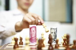 U.S. Dollar (USD) and Chinese Yuan (CNY or RMB) bills on a chess board, concept for currency games.