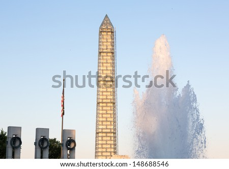 U.S. National World War II Memorial. Consisting of 56 pillars and a pair of small triumphal arches surrounding a plaza and fountain with Washington Monument in scaffolding - stock photo