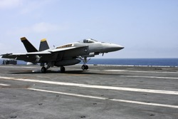 u.s navy f18 fighter jet landing on an aircraft carrier