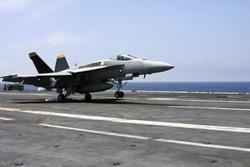 u.s navy f18 fighter jet landing on an aircraft carrier
