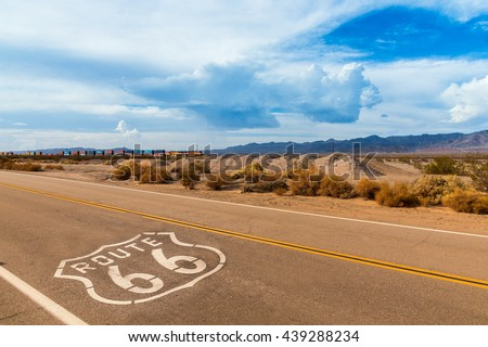 U.S. Route 66 highway, with sign on asphalt and a long train in the background, near amboy, california. Located in the mojave dessert #439288234