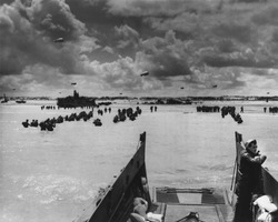 U.S. Troops land at Normandy on D-Day. With the beach taken and barrage balloons deterring German aircraft, soldiers and supplies flooded into France in June 1944, during World War 2.