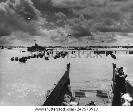 U.S. Troops land at Normandy on D-Day. With the beach taken and barrage balloons deterring German aircraft, soldiers and supplies flooded into France in June 1944, during World War 2. #249573919